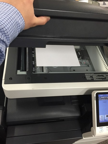 person opening the top of a copier