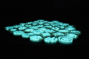 """Petri dishes """"painted"""" with living bioluminescent Photobacterium leignothi, creating self-illuminating science art.  We are not only interested in bacterial bioluminescence, but also how it can be used in artistic or outreach activities."""