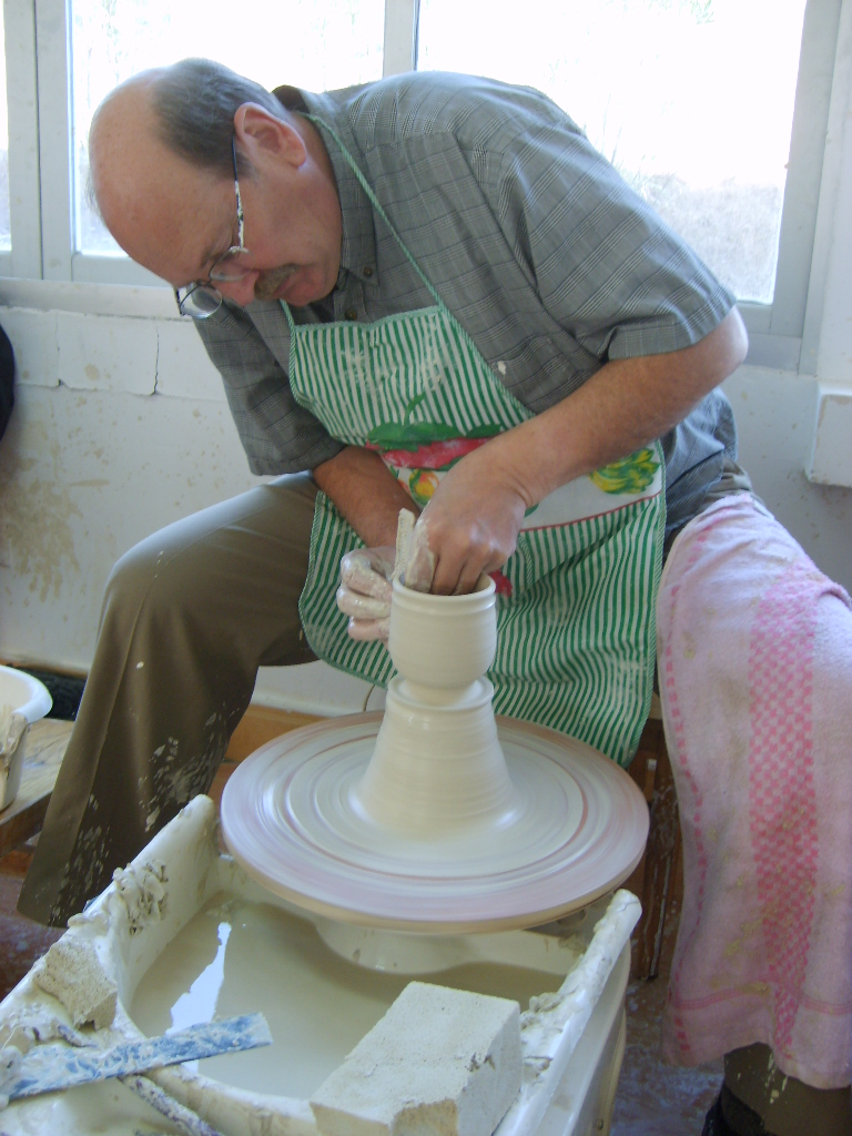 Richard Swenson M.F.A.'76, a longtime ceramics and English professor, sits at a pottery wheel. He retired this year.