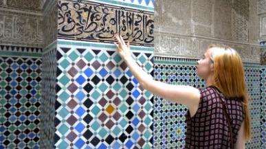 Person touching a mosaic wall