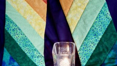 A candle and colorful quilt mosaic