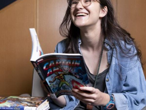 laughing student reading a book